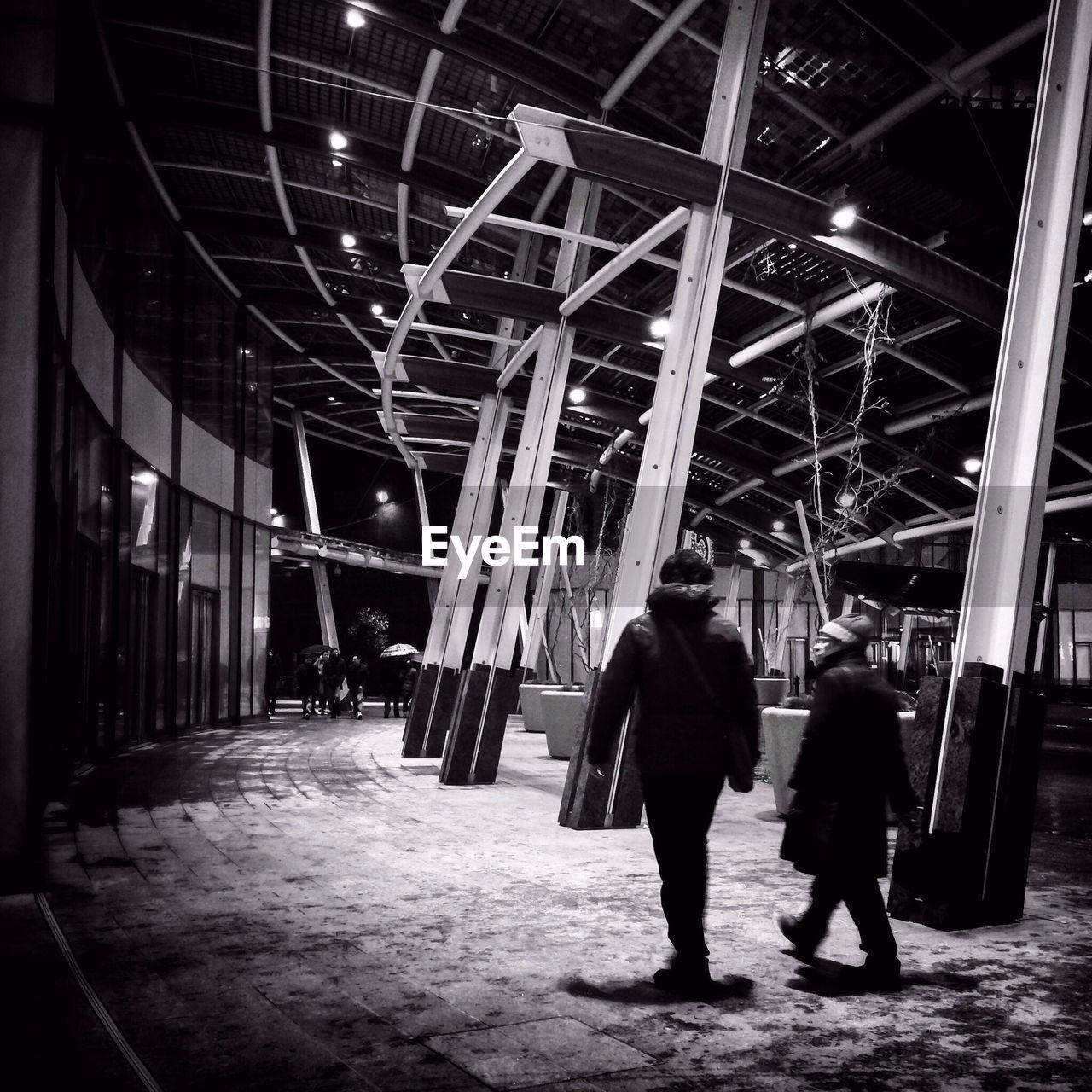 Men walking on covered street