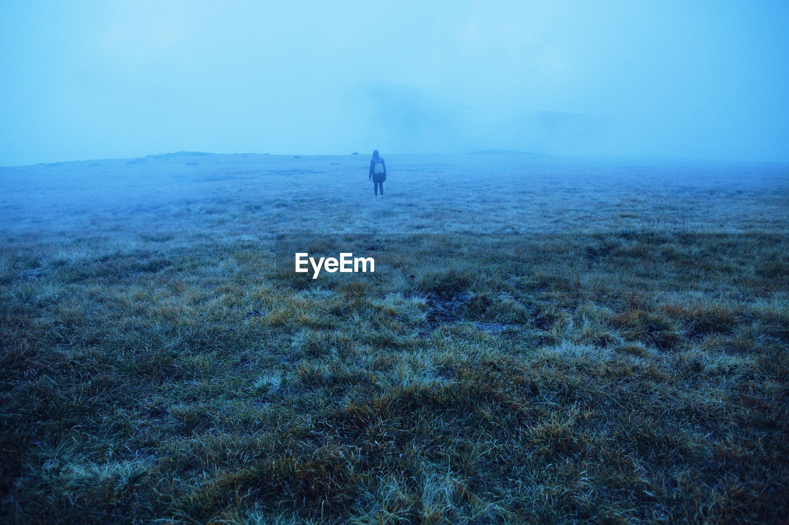 Woman with backpack standing on land during foggy weather
