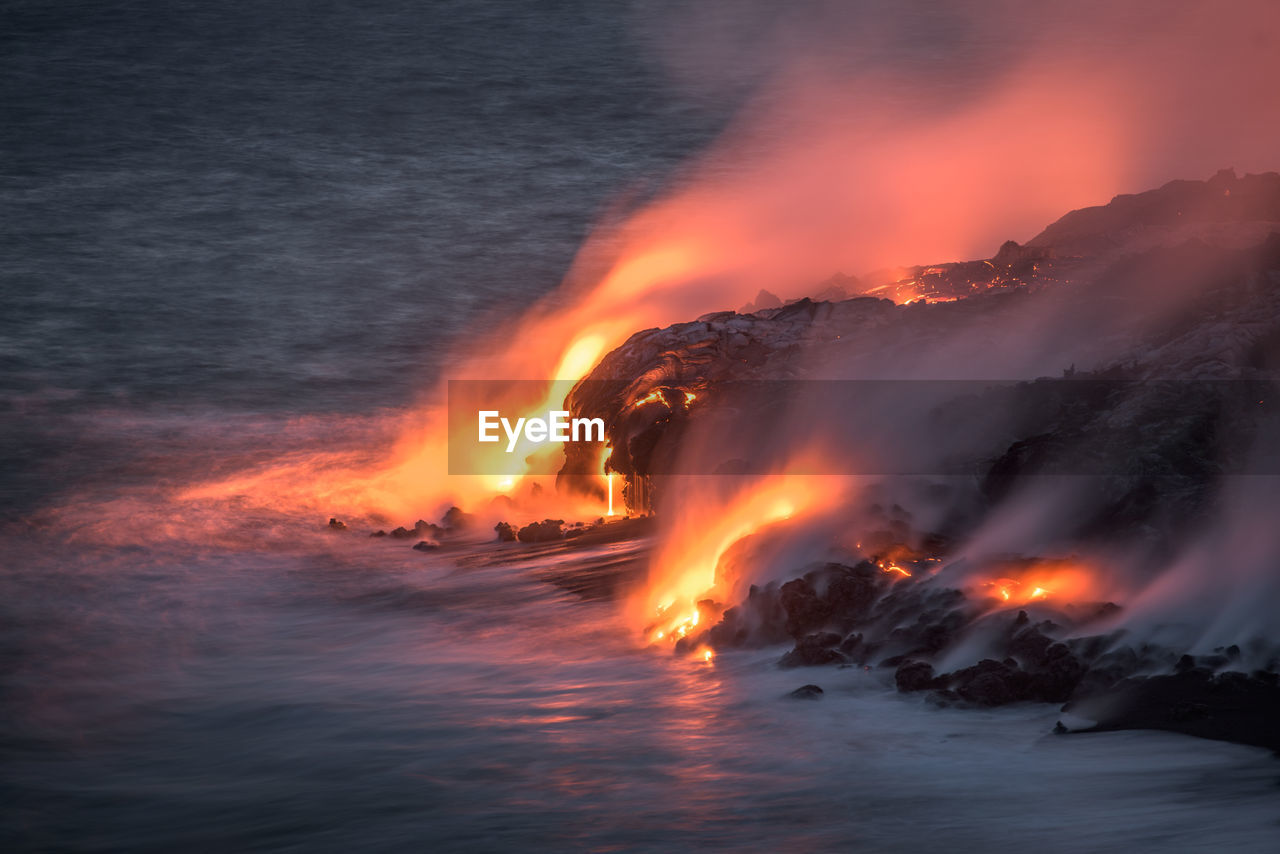 MAJESTIC VOLCANIC LANDSCAPE WITH LAVA FLOWING INTO SEA