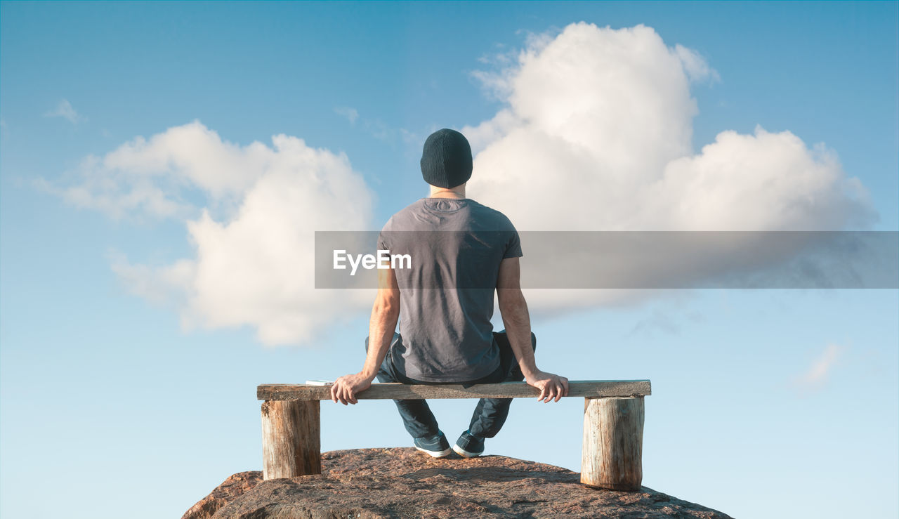 Rear view of man sitting on bench over cliff against sky