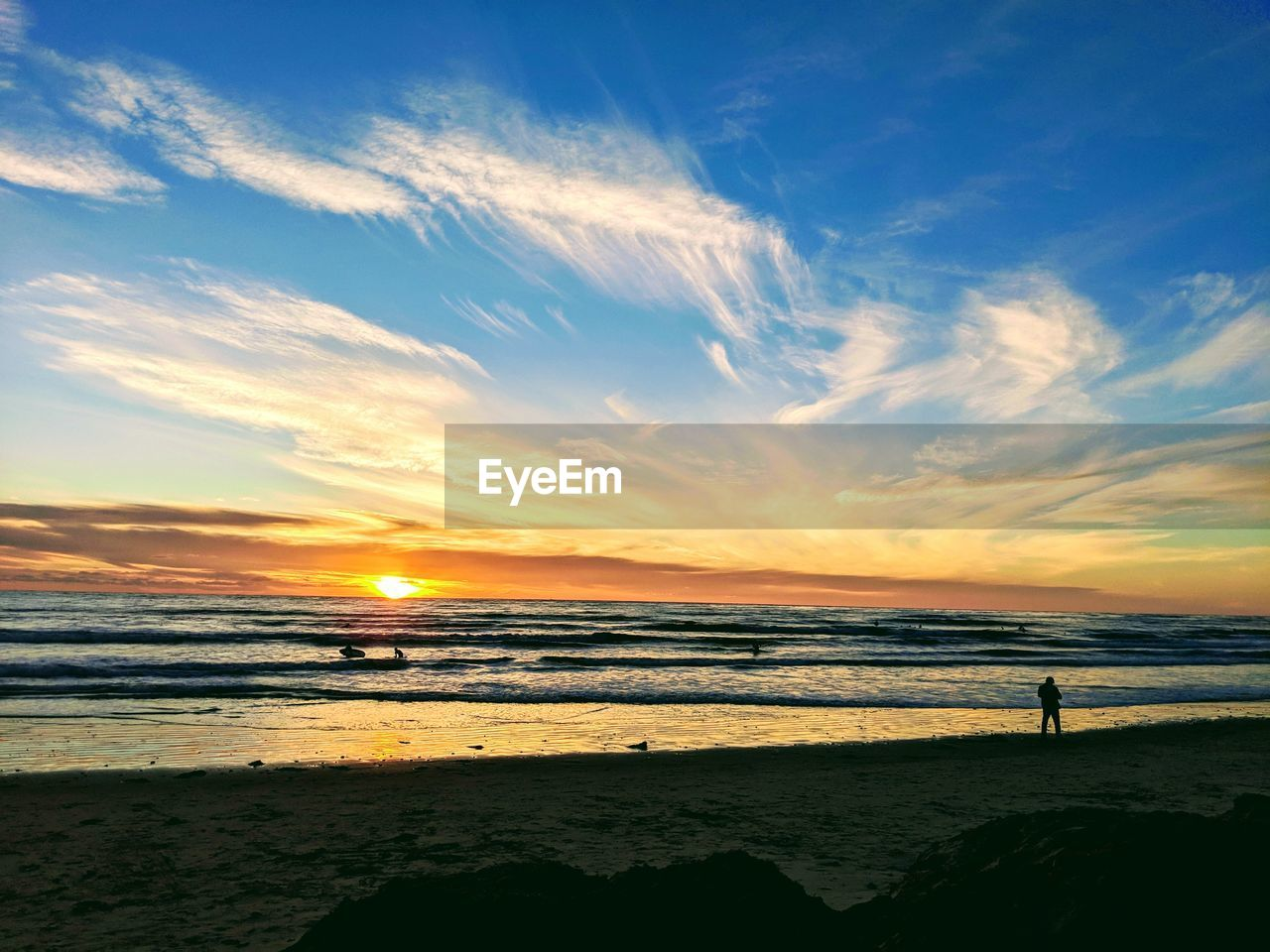sky, beach, water, sea, land, sunset, beauty in nature, scenics - nature, horizon over water, cloud - sky, horizon, tranquility, tranquil scene, silhouette, idyllic, real people, standing, nature, orange color, outdoors
