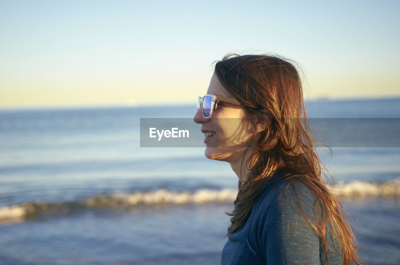Smiling Young Woman Wearing Sunglasses At Beach Against Sky During Sunset