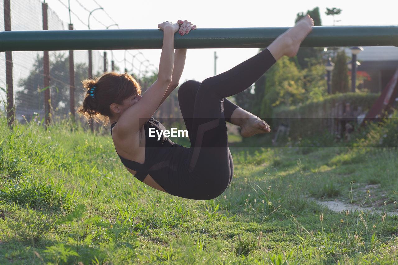 Side view of woman exercising on metallic railing