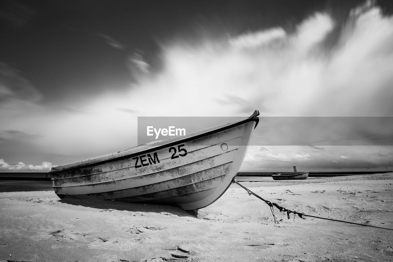 nautical vessel, cloud - sky, mode of transportation, sky, transportation, beach, water, moored, nature, land, sea, no people, western script, day, text, scenics - nature, beauty in nature, sand, outdoors, fishing boat