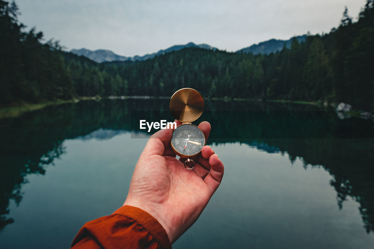 Cropped hand holding compass against lake in forest