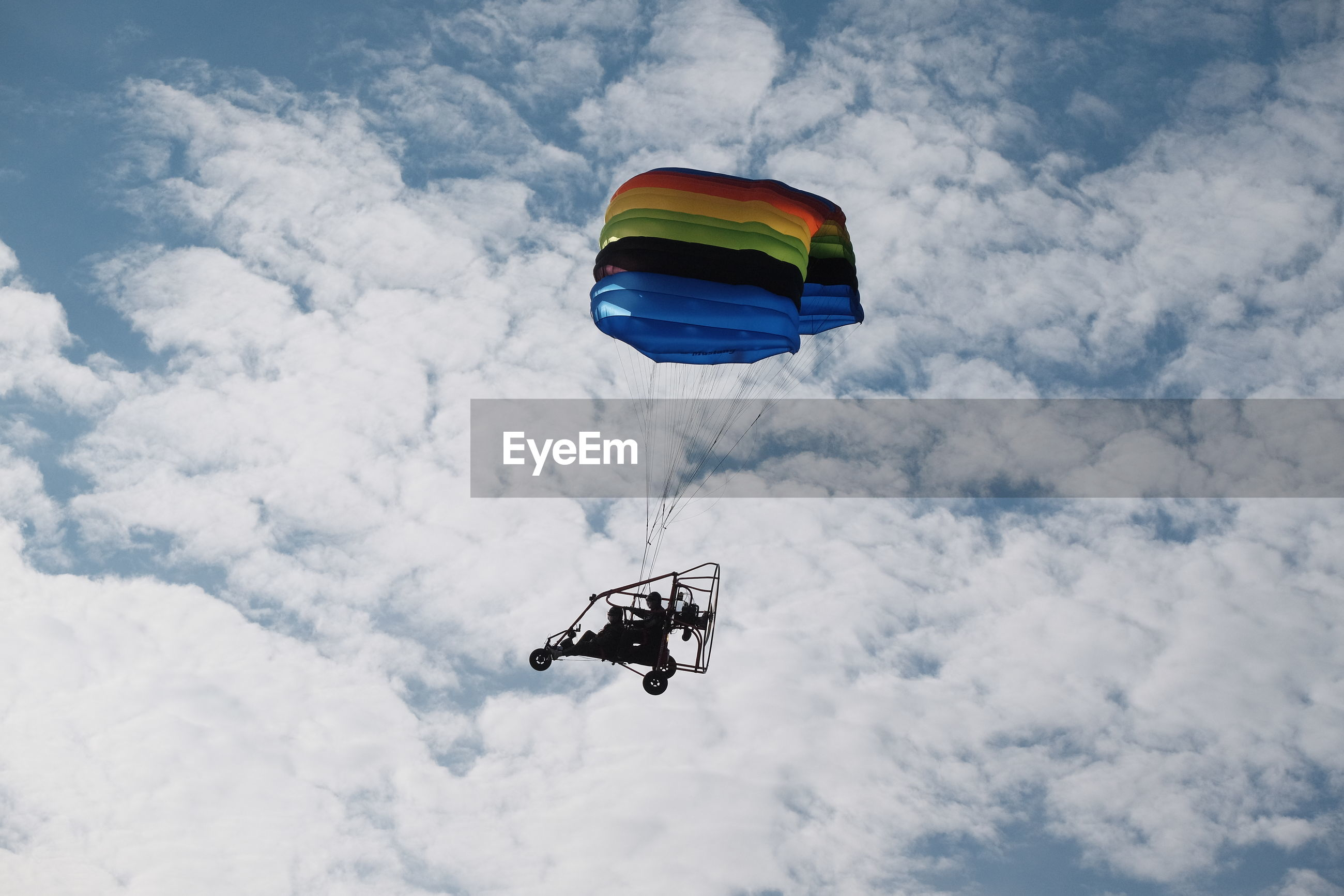 Low angle view of people powered paragliding against cloudy sky