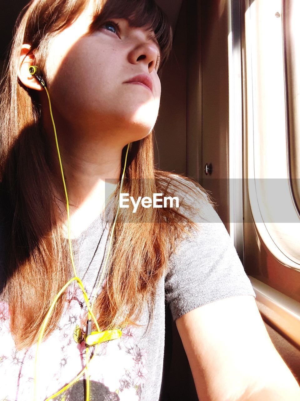 Close-Up Of Young Woman Listening Music While Traveling In Train