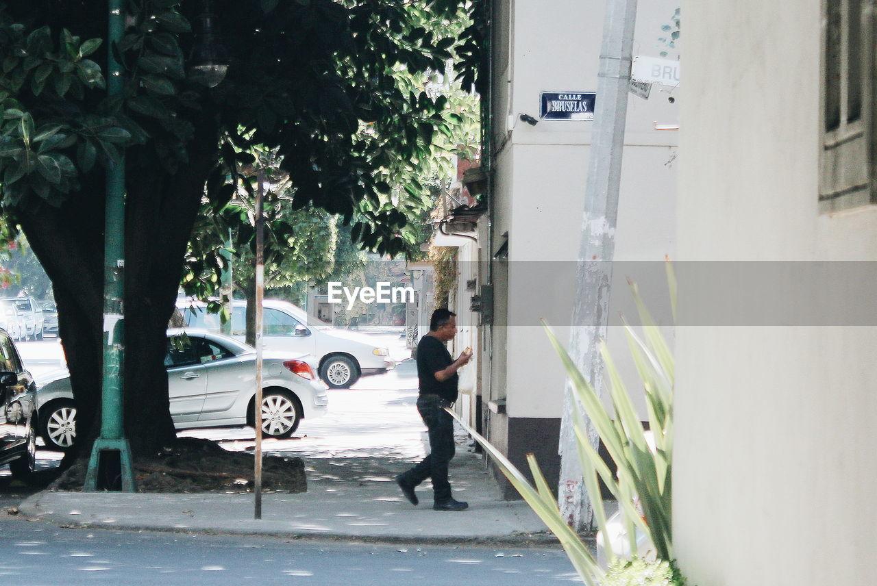 MAN WALKING ON STREET AGAINST CITY