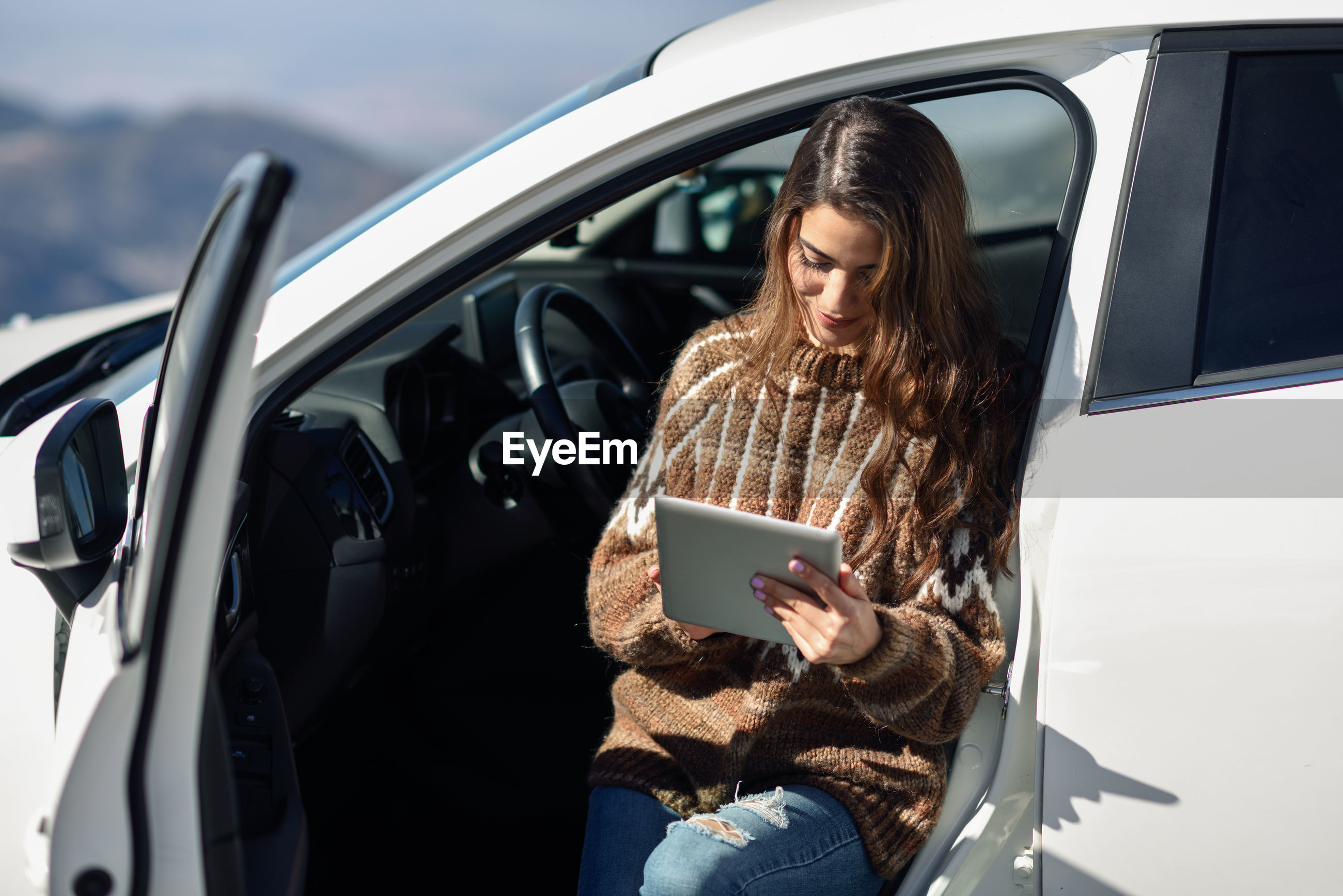 Young woman using digital tablet while leaning on car