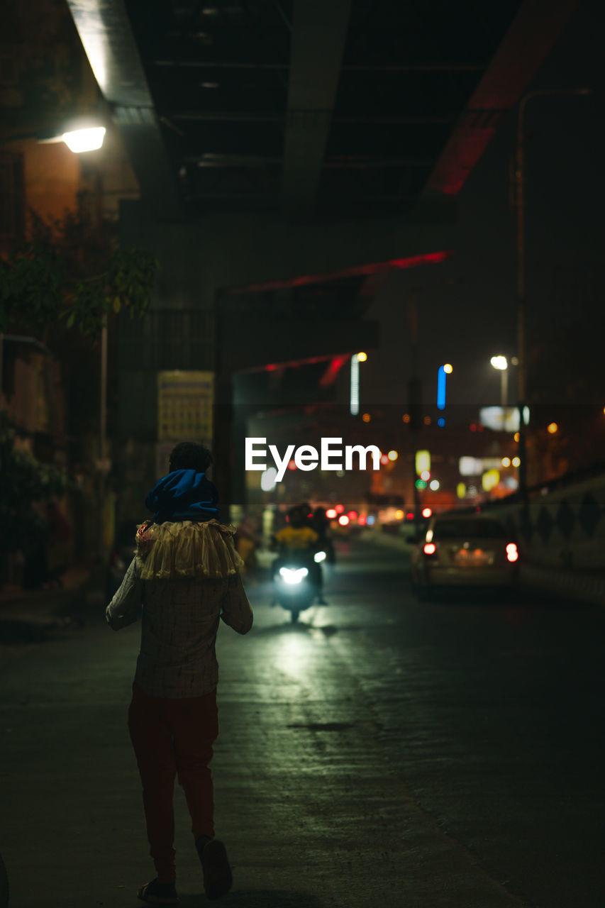 FULL LENGTH REAR VIEW OF WOMAN WALKING ON ILLUMINATED STREET AT NIGHT