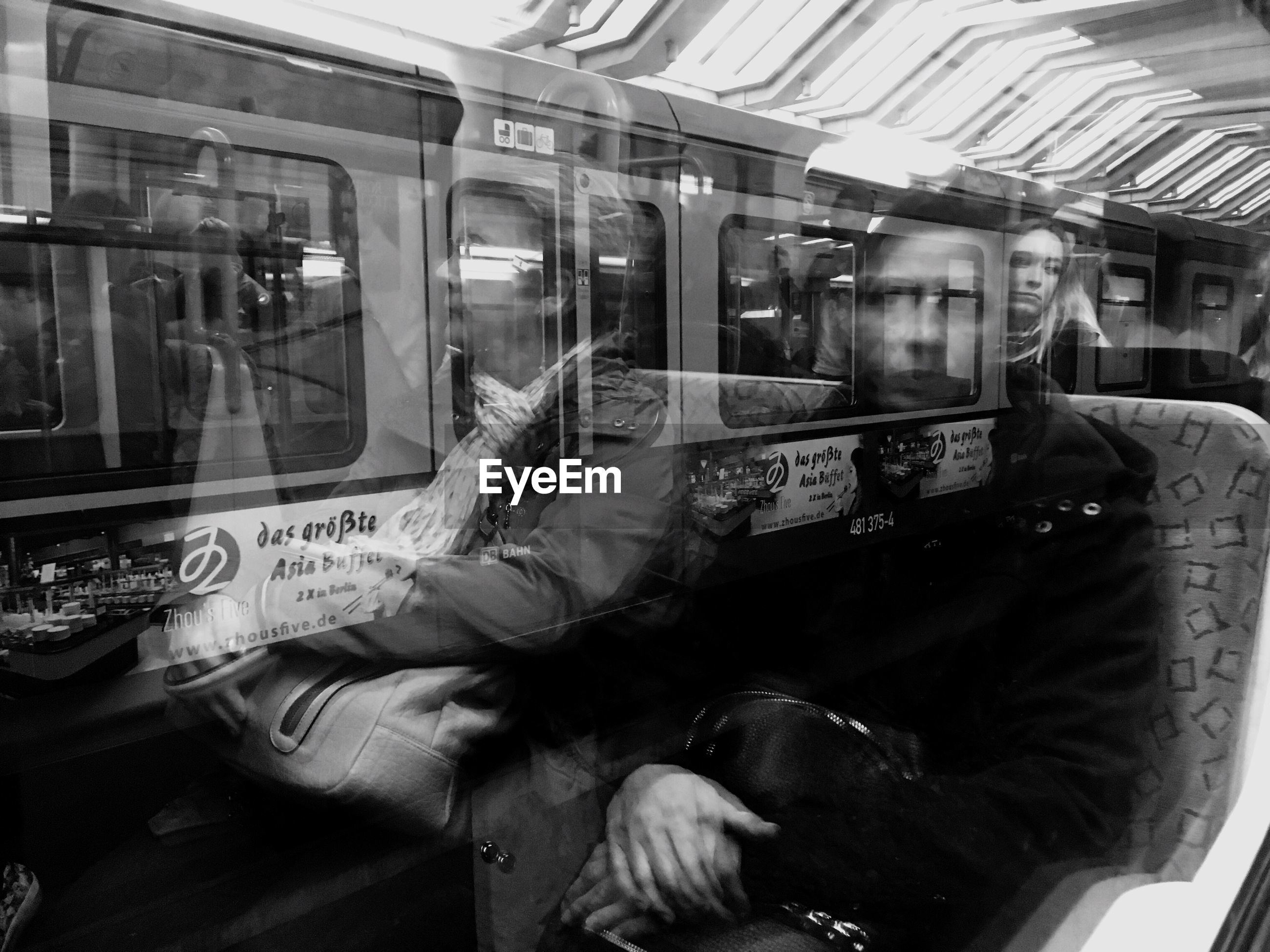 REFLECTION OF MAN SITTING IN TRAIN AT BUS