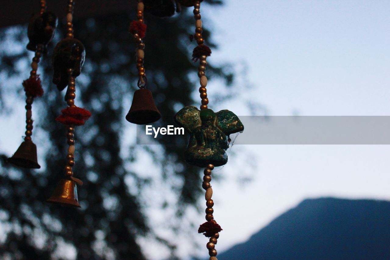 Low angle view of wind chime hanging against sky