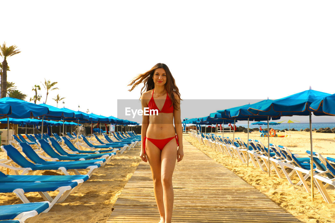 Portrait Of Young Woman Wearing Red Bikini While Standing On Boardwalk At Beach Against Clear Sky