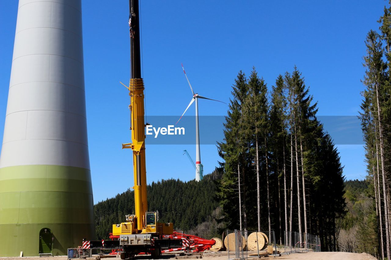 Construction machine by windmills on field against clear blue sky