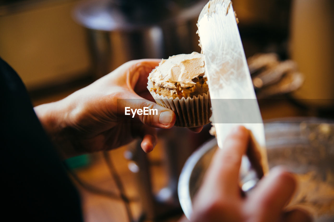 Close-Up Of Person Icing Cupcake