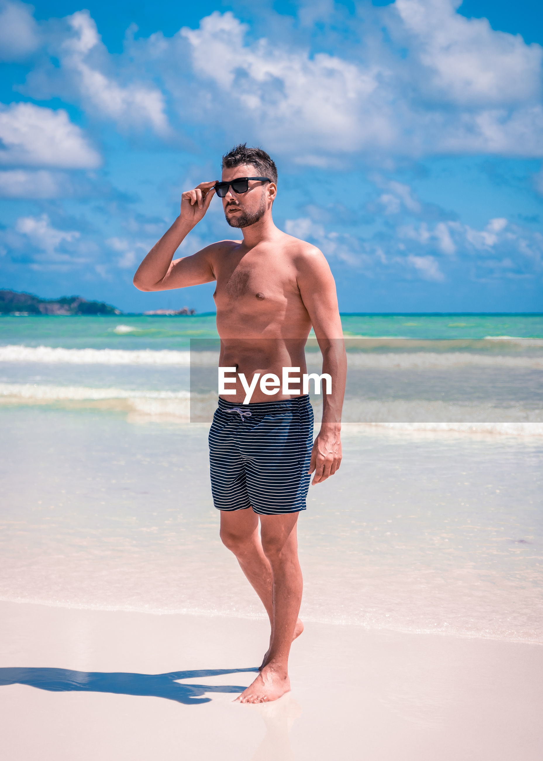 Full length of shirtless man in sunglasses walking at beach against sky