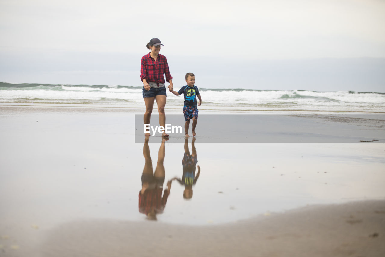 FULL LENGTH OF FATHER AND DAUGHTER ON BEACH