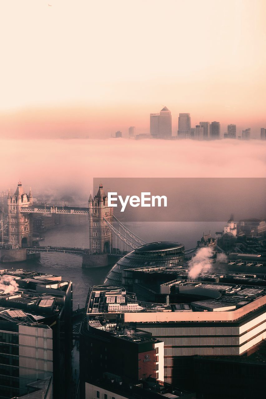 High angle view of city by river at sunset during foggy weather