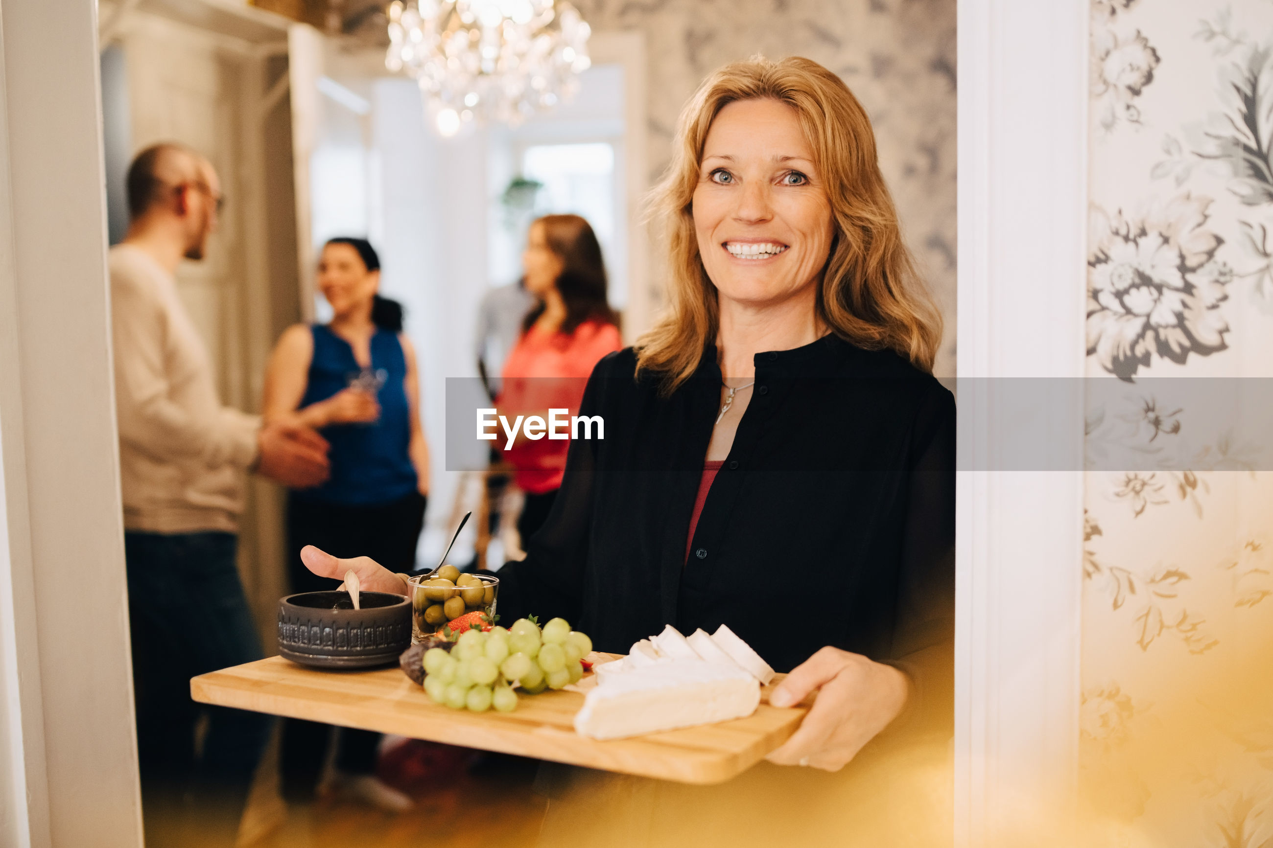 YOUNG WOMAN STANDING BY CAKE WITH FACE