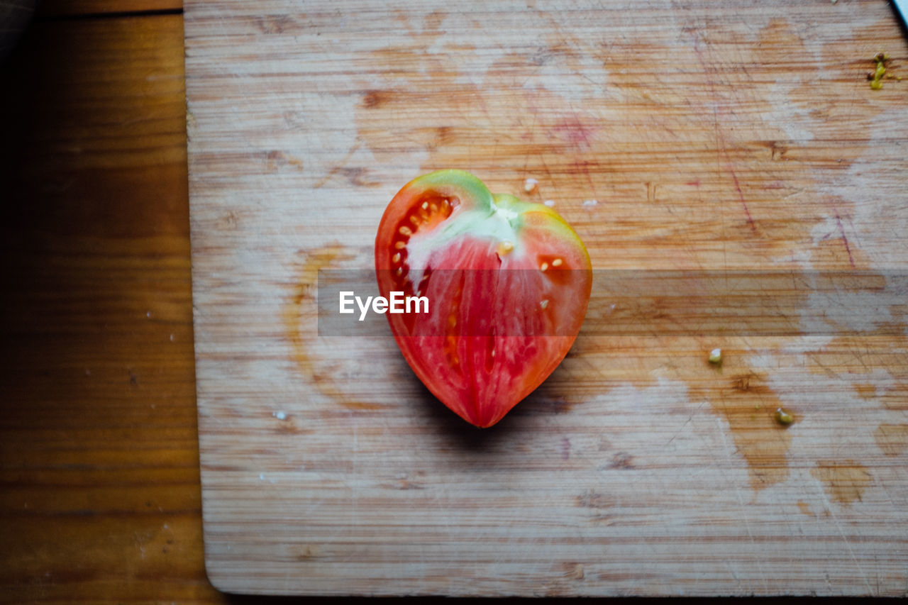 High angle view of heart shape tomato on cutting board