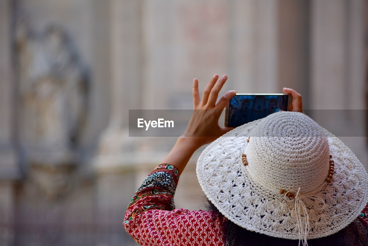 Rear View Of Woman Wearing Hat While Photographing With Mobile Phone