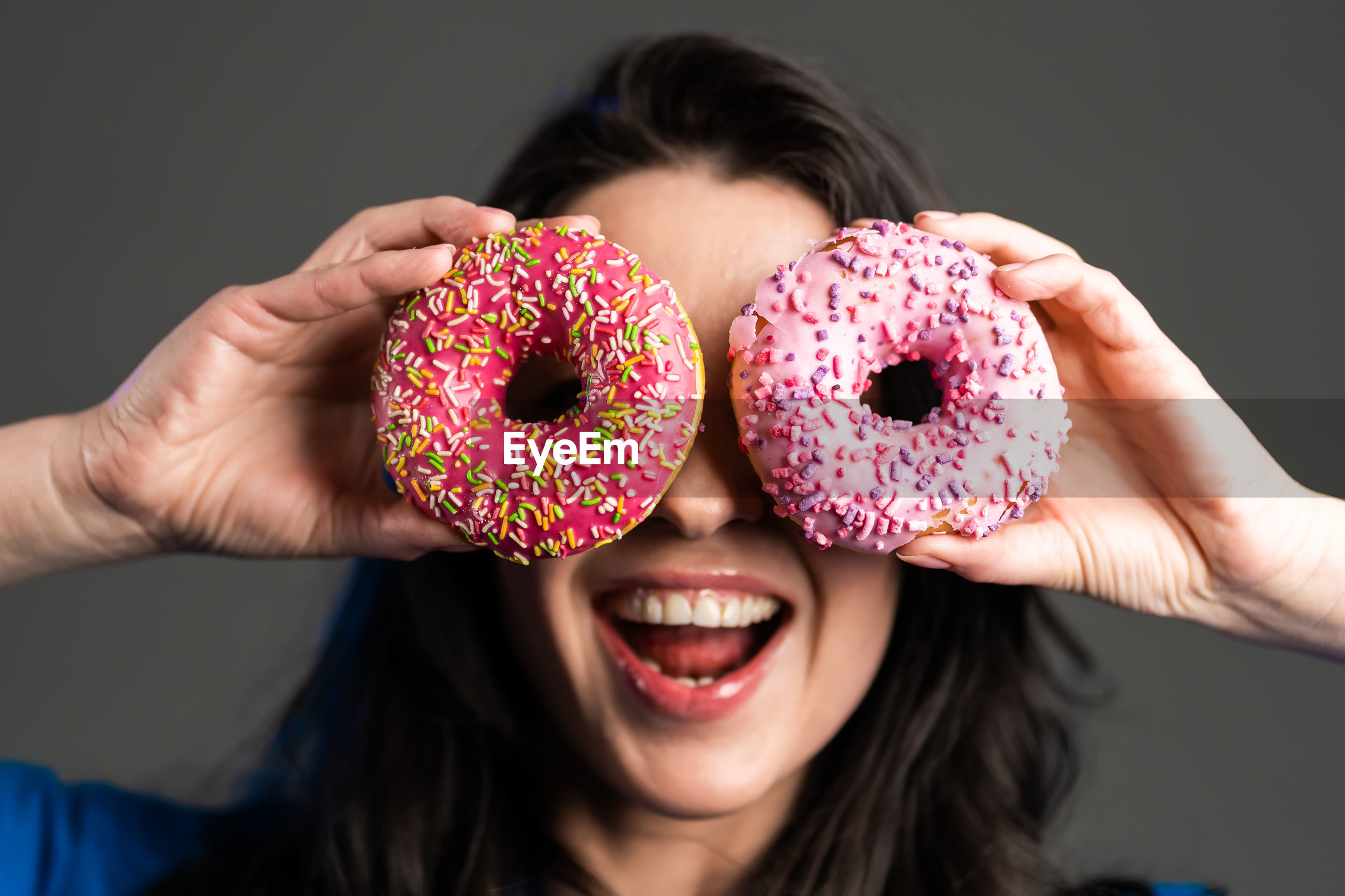 Woman holding donuts against gray background
