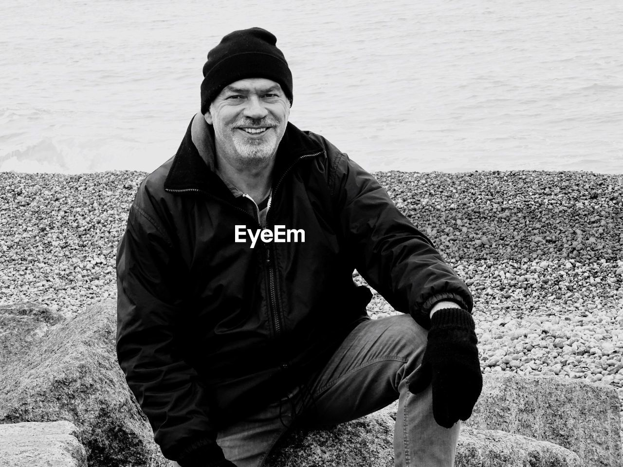 Portrait Of Smiling Man Sitting On Rock At Beach