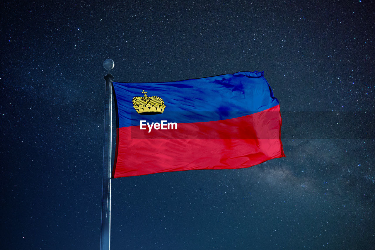 Flag of liechtenstein against star field sky