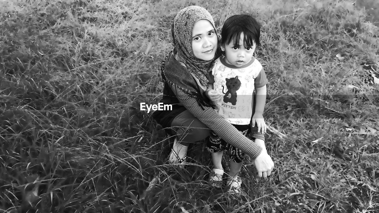 Portrait of mother and daughter on field