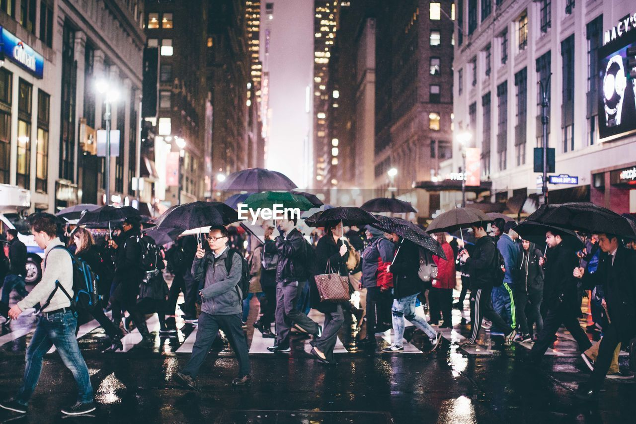 umbrella, city, building exterior, group of people, architecture, street, wet, protection, city life, rain, built structure, night, real people, crowd, large group of people, nature, walking, transportation, water, city street, outdoors, rainy season