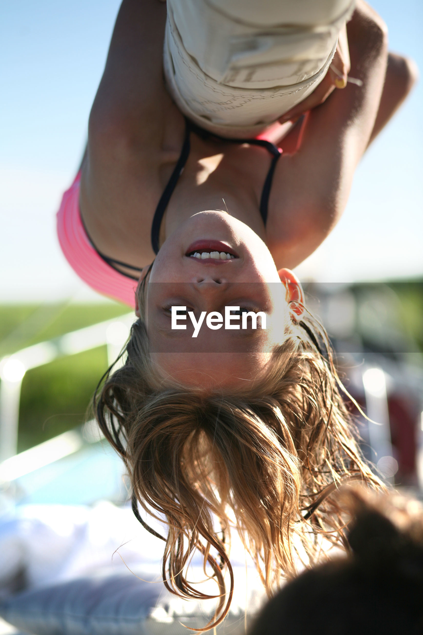 Close-up portrait of teenage girl hanging upside down at playground