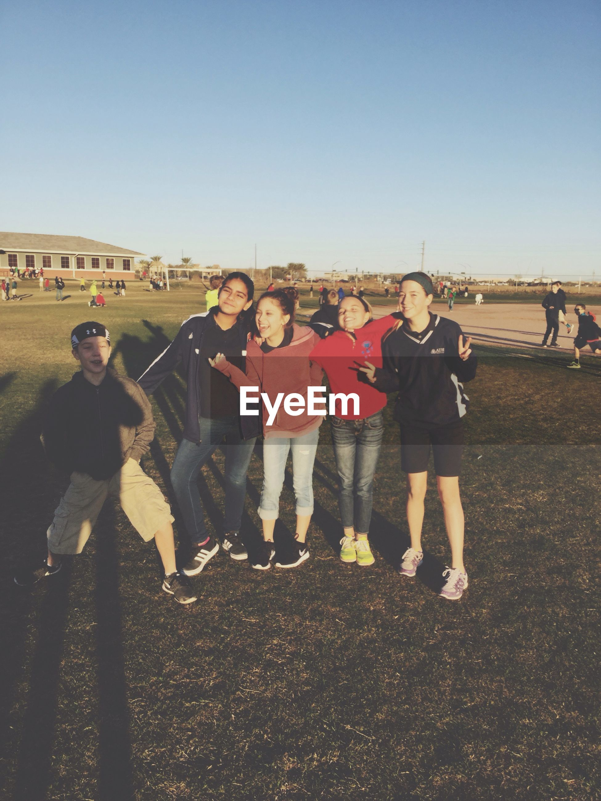 lifestyles, leisure activity, togetherness, clear sky, men, large group of people, person, friendship, casual clothing, bonding, copy space, love, standing, enjoyment, full length, fun, field, outdoors, boys