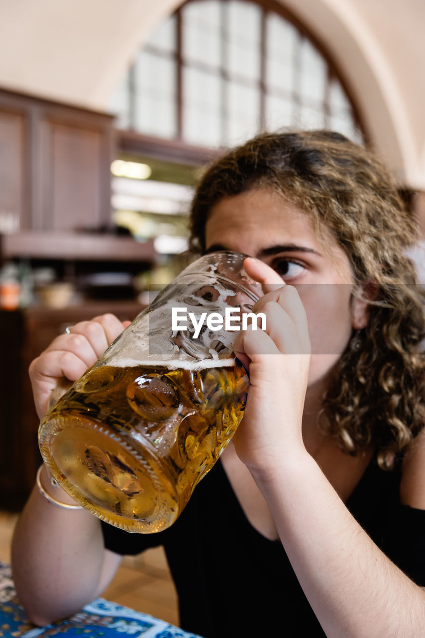 Close-up of young woman drinking beer at restaurant