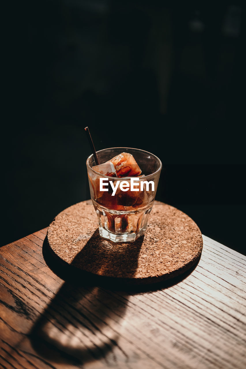 Close-Up Of Drink In Glass On Table Against Black Background