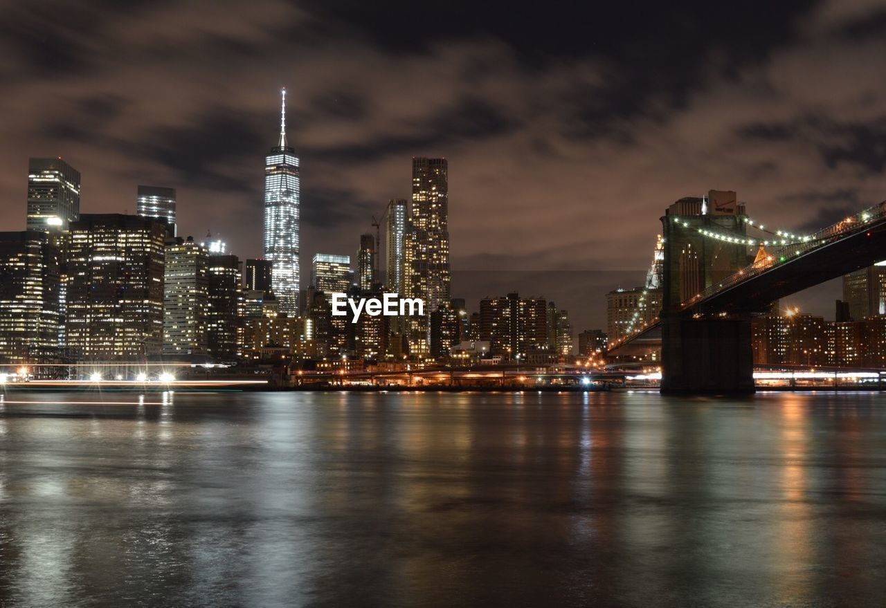 Low angle view of illuminated one world trade center and brooklyn bridge by river