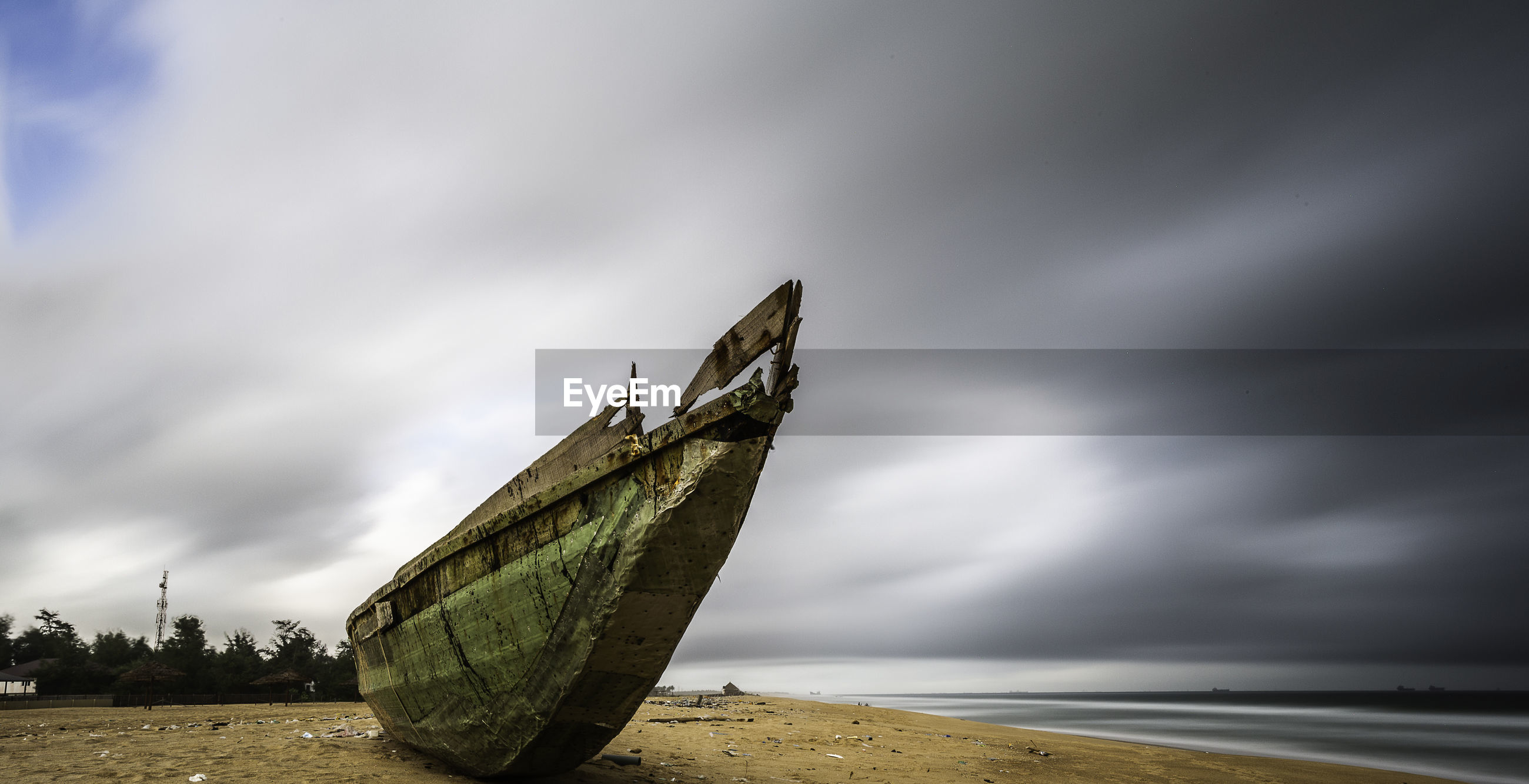 Abandoned boat moored on beach against sky