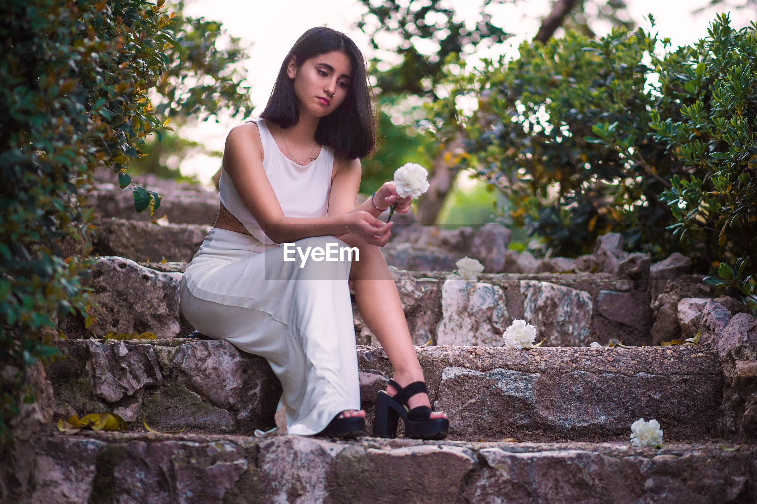 Full length of young woman holding flower while sitting on steps