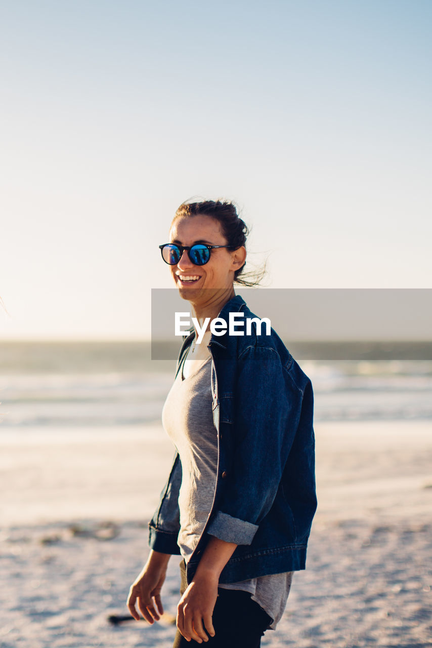 Portrait of smiling woman standing at beach against sky