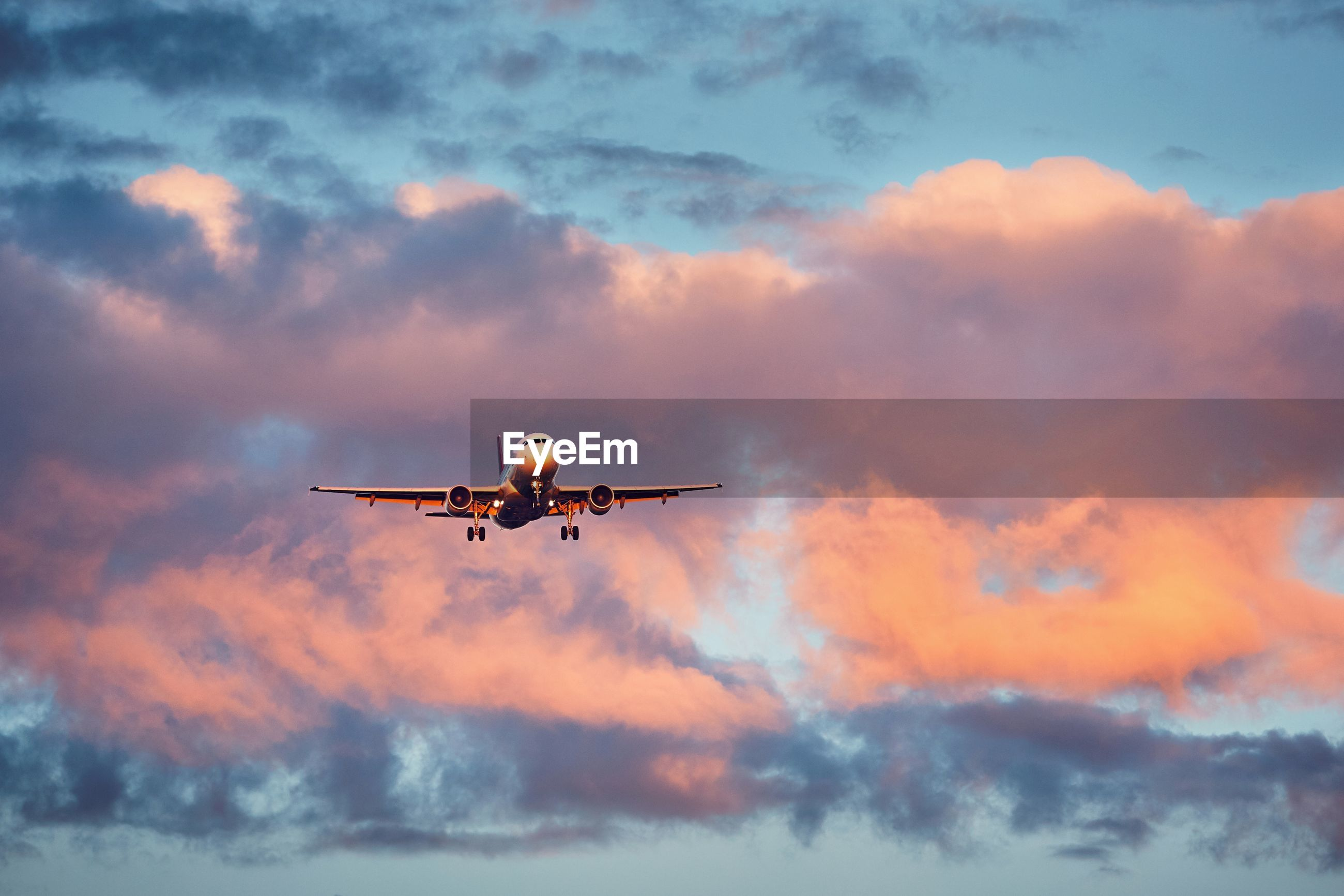 Low angle view of airplane flying at sunset