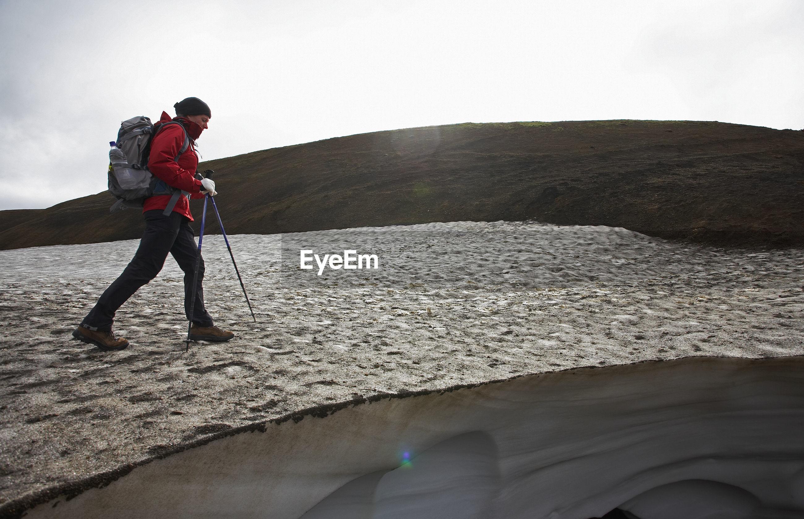 FULL LENGTH OF MAN STANDING IN MOUNTAINS AGAINST SKY