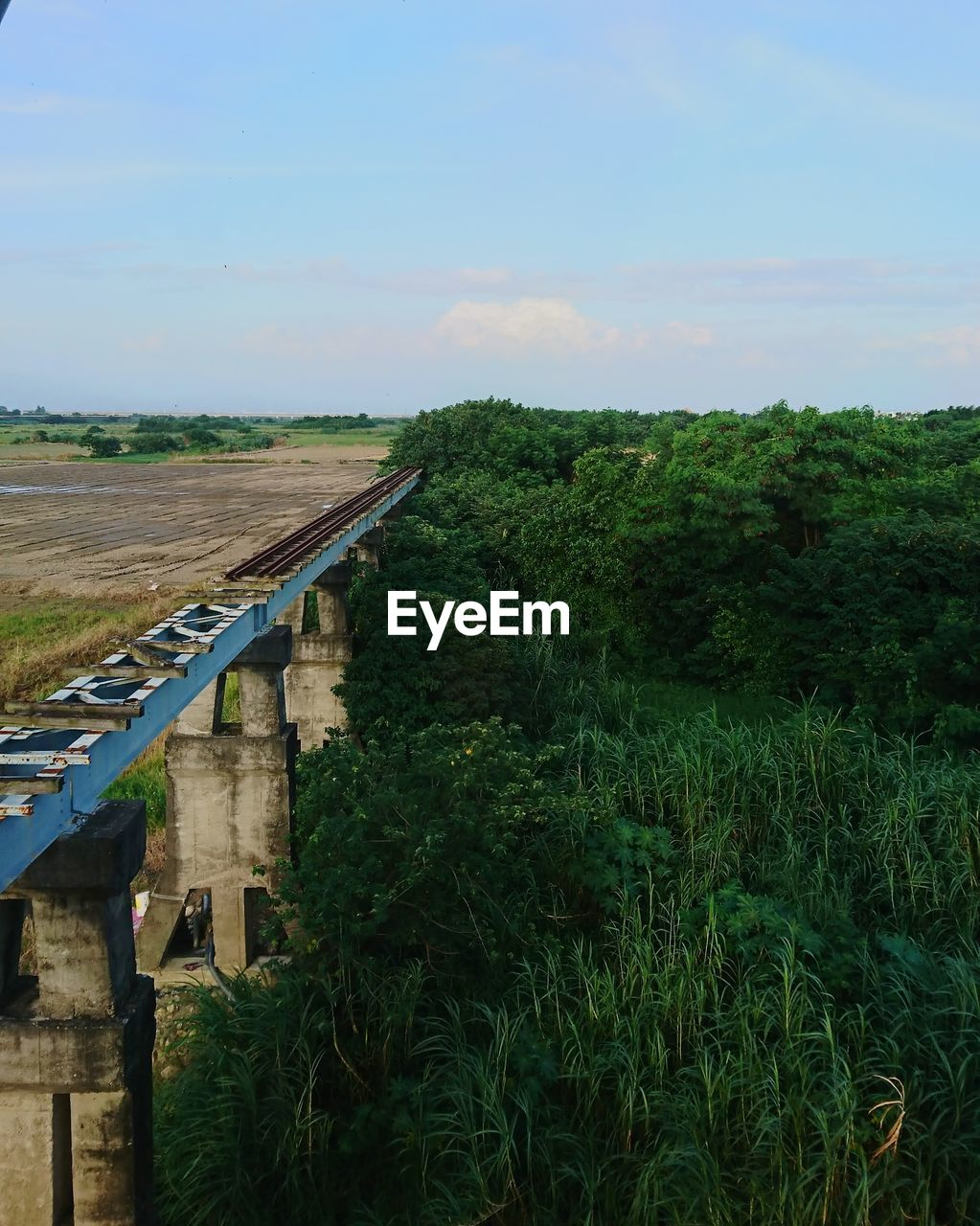 sky, plant, nature, green color, architecture, growth, transportation, landscape, built structure, rail transportation, tree, no people, day, land, beauty in nature, environment, field, outdoors, scenics - nature, cloud - sky