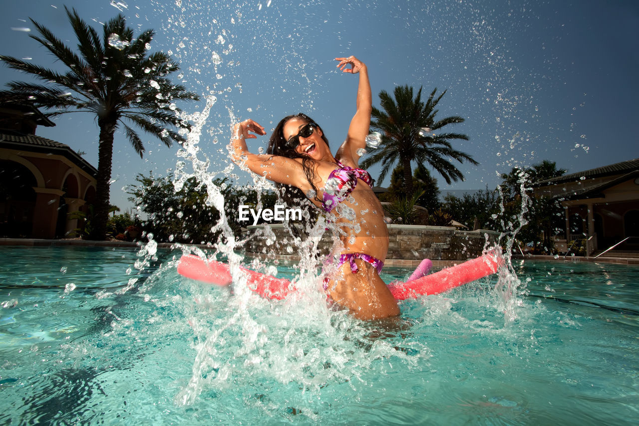 water, swimming pool, pool, fun, enjoyment, tree, motion, nature, happiness, emotion, one person, leisure activity, splashing, arms raised, young adult, swimwear, smiling, palm tree, human arm, positive emotion, limb, human limb, excitement, outdoors