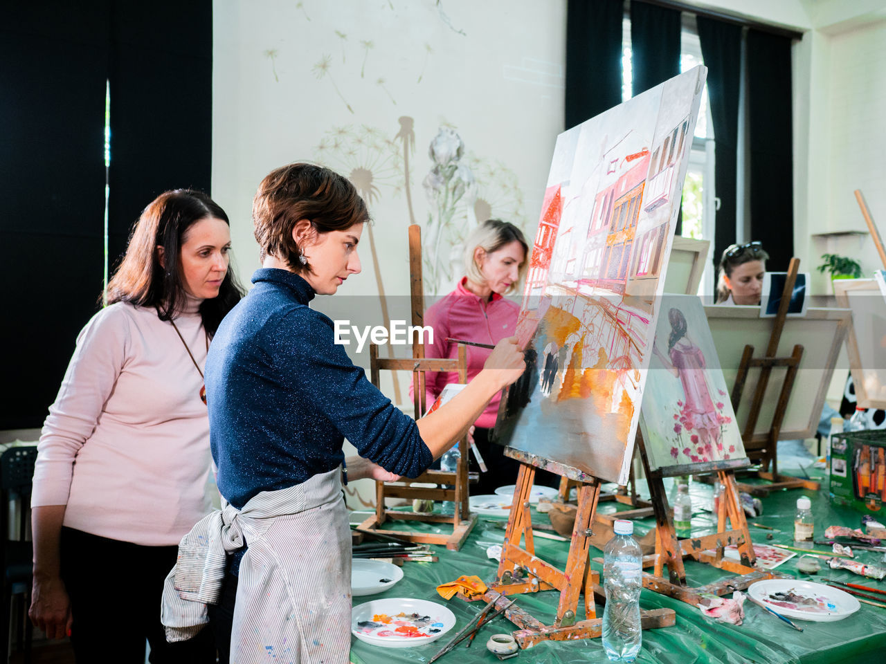 Woman Looking At Painter Painting In Studio