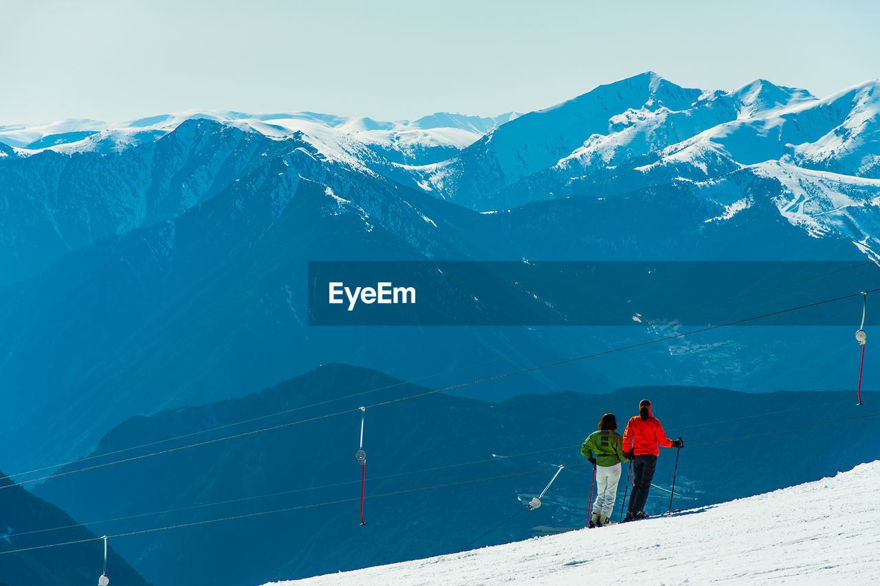 VIEW OF SKI LIFT AGAINST MOUNTAIN RANGE