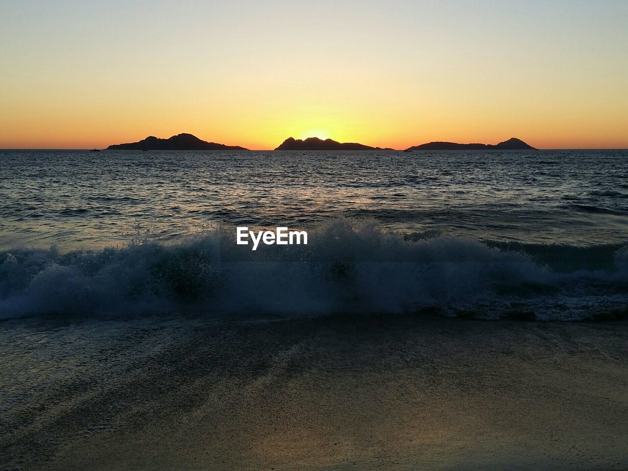 sea, sunset, beauty in nature, water, wave, scenics, nature, beach, no people, outdoors, tranquility, sky, tranquil scene, clear sky, sand, horizon over water, mountain, day