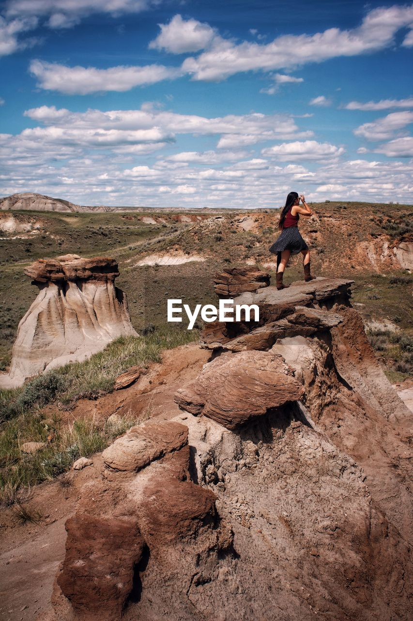 Full length of young woman on rock hoodoo in badlands