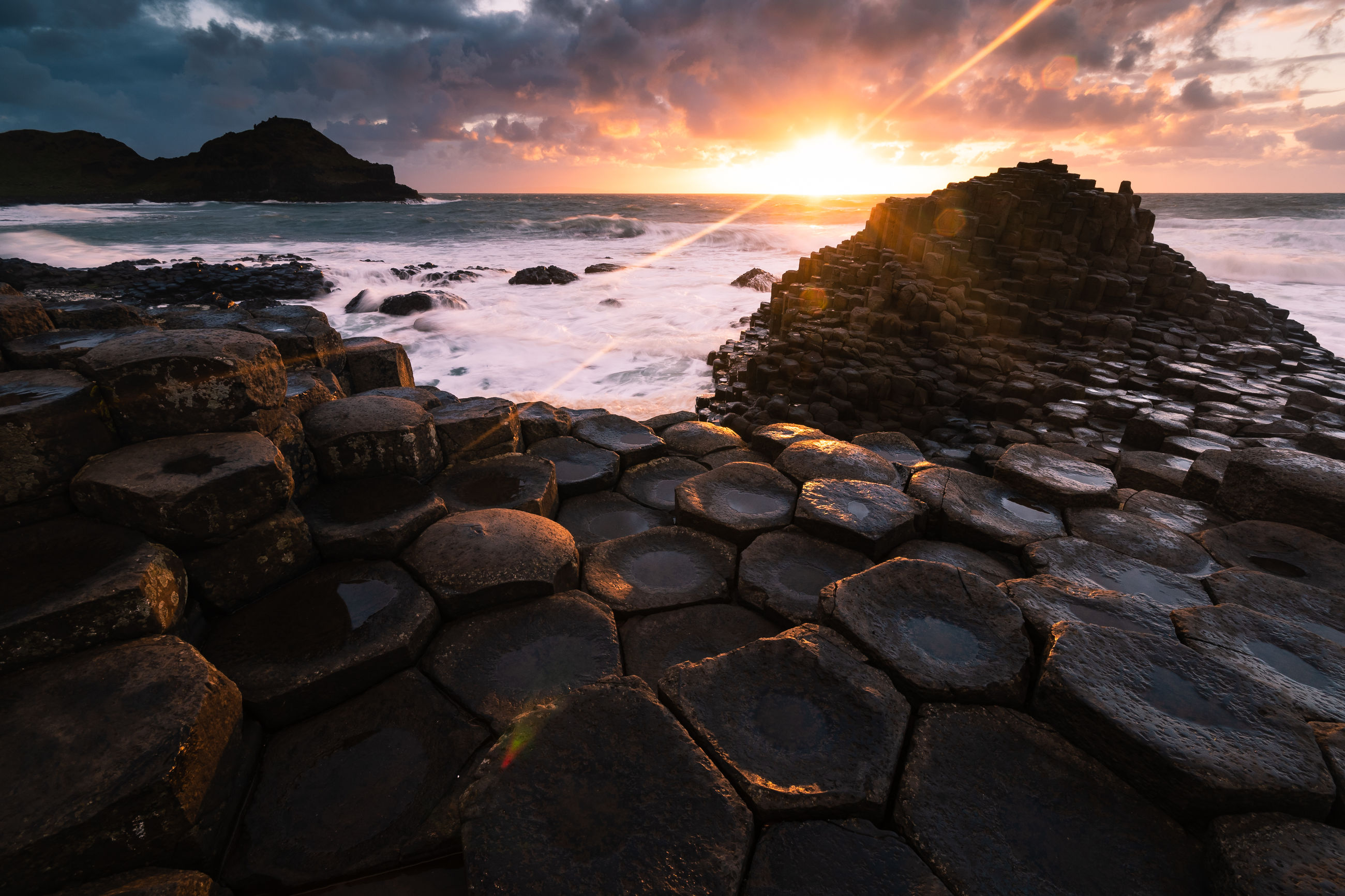 ROCKS ON SEA SHORE AGAINST SUNSET SKY