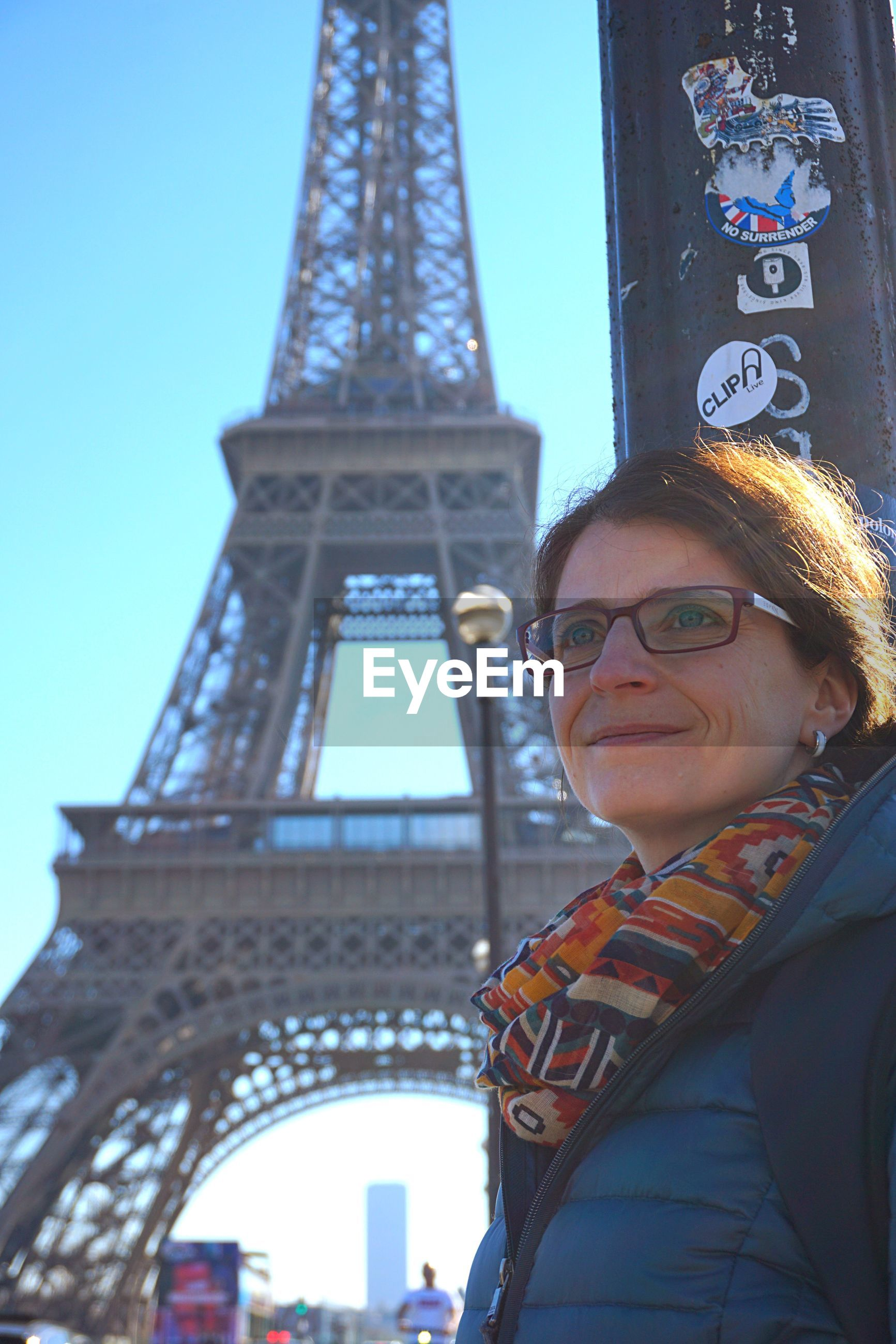Smiling woman looking away against eiffel tower