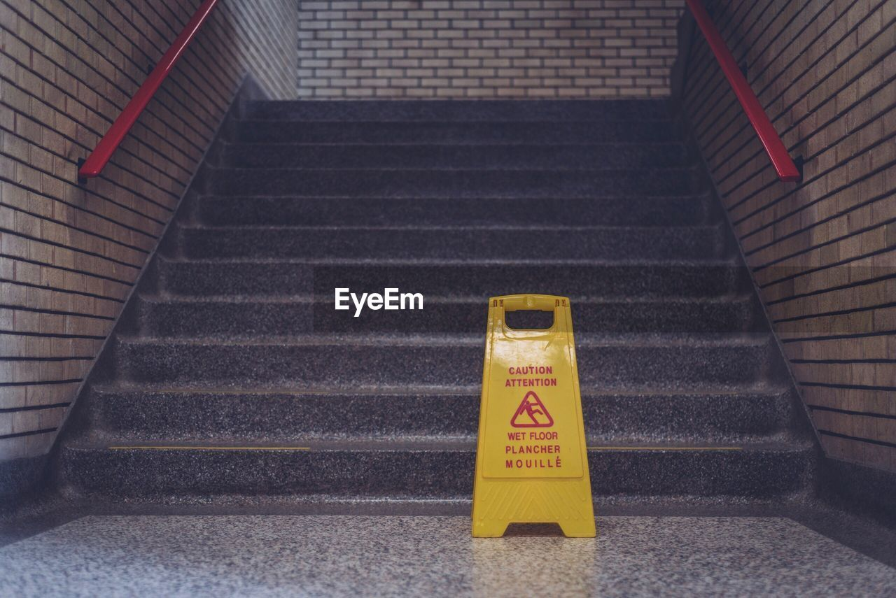 High Angle View Of Wet Floor Sign By Steps