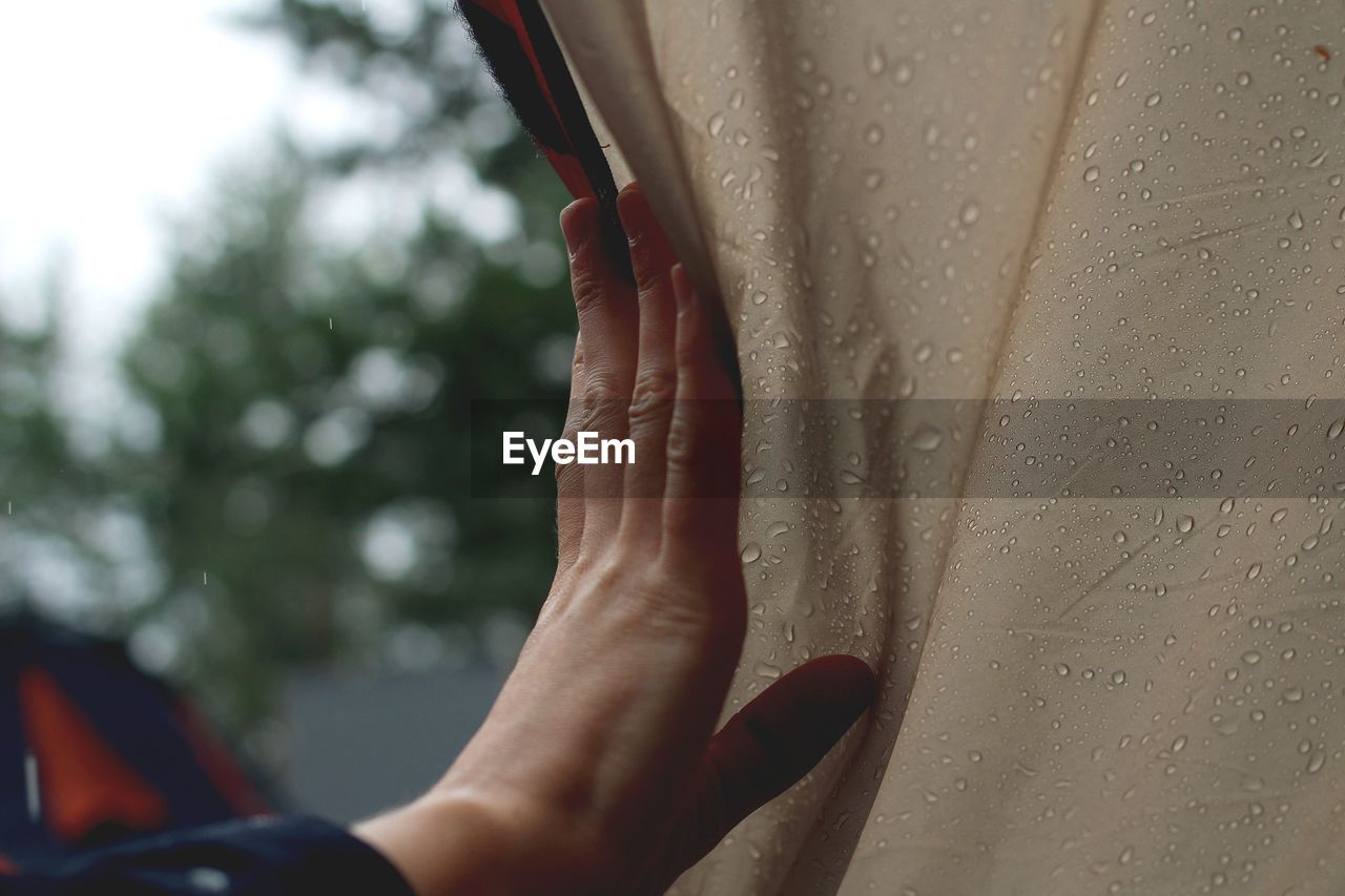 Close-Of Hand Touching Wet Tent